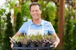genietend van zijn werk met planten. foto