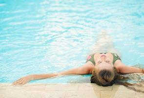 jonge vrouw genieten van zwembad. achteraanzicht foto