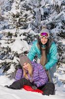 twee tienervrienden genieten van bobsleeën in de wintersneeuw foto