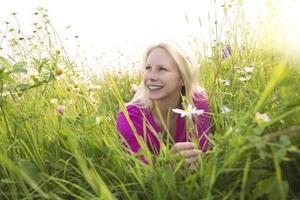 mooie vrouw genieten van daisy in een veld foto