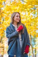 vrouw genieten van de kleurrijke gele bladeren vallen