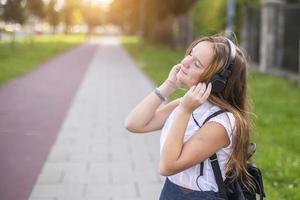 schattig meisje genieten van muziek met een koptelefoon buitenshuis. foto