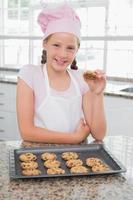 glimlachend jong meisje dat van koekjes in keuken geniet