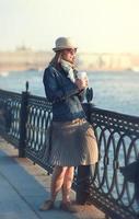 mooie vrouw in muts en sjaal genieten van zonlicht foto