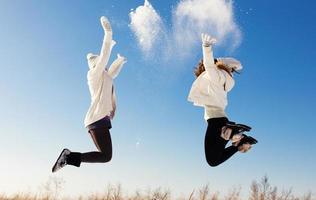 twee vriendinnen hebben plezier en genieten van verse sneeuw foto
