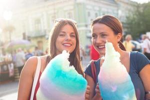 jonge vrouwen die suikerspin houden en openlucht van genieten