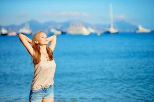 jong meisje genieten van haar vakantie aan zee foto