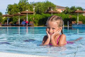 schattig gelukkig meisje genieten van zwemmen in het zwembad foto