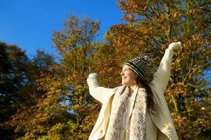 gelukkige vrouw glimlachend en genieten van een herfstdag buitenshuis foto