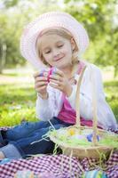 schattig jong meisje met hoed geniet van haar paaseieren foto