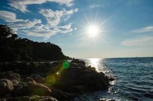 zonsondergang achtergrondverlichting op de kust foto
