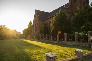 lichtstraal in een groen park naast een kerk foto