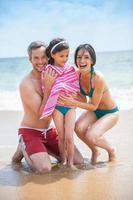 portret van een jong stel in zwemkleding met hun dochter foto