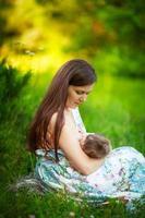 moeder voedt de baby, borstvoeding, zomer foto