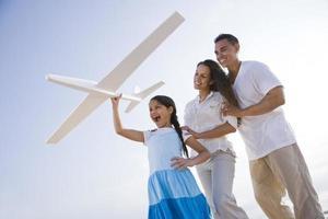 Spaanse familie en meisje met plezier met speelgoed vliegtuig foto