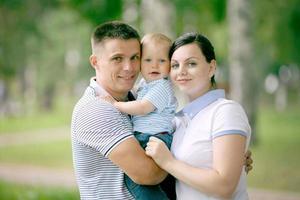 gelukkige jonge familie moeder vader en baby in het park foto