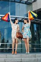 twee aantrekkelijke vrouwen poseren met boodschappentassen foto