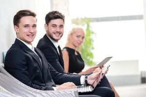sollicitanten. drie mensen in formalwear wachten in kantoor foto