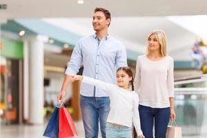 vriendelijke familie wandelen rond winkelcentrum foto