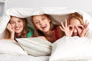 gelukkige jonge vrouwen in bed thuis pyjama party foto