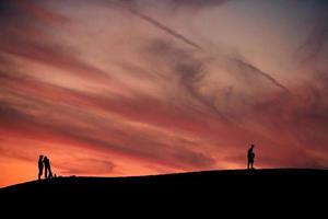 mensen in de zonsondergang, silhouet foto