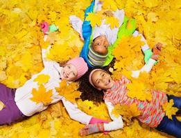 kinderen spelen met herfst esdoorn oranje bladeren foto