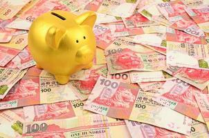 gouden spaarvarken op geldachtergrond foto