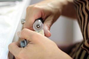 tandtechnicus verwerkt de kunsttanden met micromotor foto