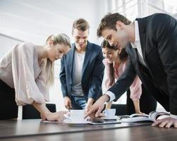 jonge mensen uit het bedrijfsleven brainstormen aan vergadertafel foto
