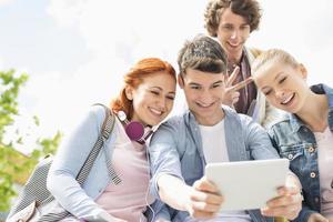 jonge vrienden die zichzelf fotograferen via een digitale tablet op de campus van de universiteit foto