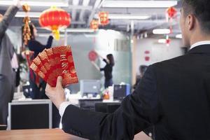 zakenman die rode enveloppen houdt voor Chinees nieuw jaar foto