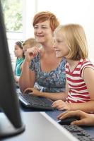 vrouwelijke basisschoolleerling in computerklas met leraar foto