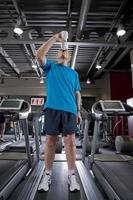 man drinken uit een fles water op de loopband in de healthclub foto