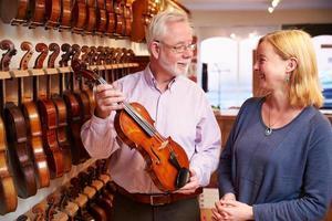 verkoper adviseert klant het kopen van viool foto
