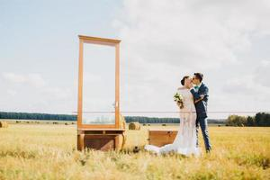 bruidegom kussen bruid in veld foto