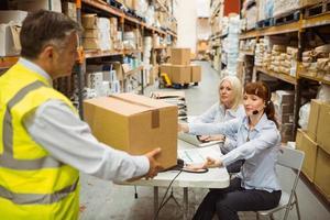 manager die geel vest draagt dat doos geeft aan zijn collega