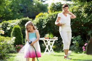 meisje en oma drenken bloemen in de tuin foto
