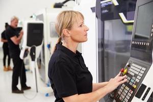 vrouwelijke ingenieur die cnc machines op fabrieksvloer in werking stelt