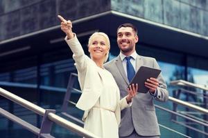 lachende zakenlieden met tablet pc buitenshuis foto
