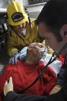 brandweerman en paramedicus die de mens in ambulance helpt foto