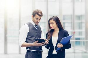 mensen uit het bedrijfsleven praten en kijken naar een tablet in een kantoor
