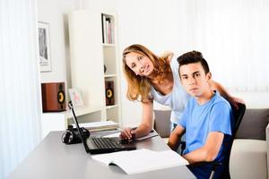 vrolijke jonge vrouw privéleraar die een tiener helpt die huiswerk doet foto