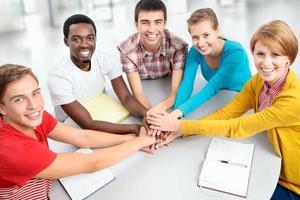verenigde studenten staken allemaal hun handen in het midden foto