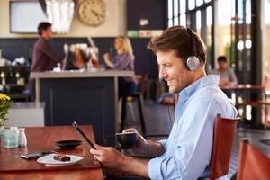 man met behulp van digitale tablet in een koffieshop foto