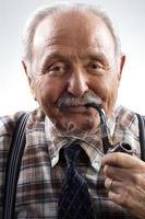senior man een pijp roken foto