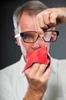 expressieve senior man tegen grijze muur. zijn bril schoonmaken. foto