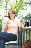 vrouw in de achtertuin met koffie en koekjes foto