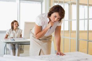 zakenvrouw bezig met blauwdrukken met collega op achtergrond op kantoor foto