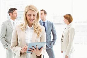 zakenvrouw met behulp van digitale tablet met collega's achter foto