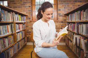 glimlachende leraar die een boek leest foto